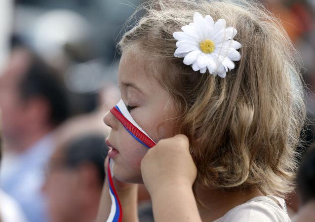 Menina brinca com uma fitinha pintada nas cores da bandeira da Rússia durante a EXPO 2015, em Milão