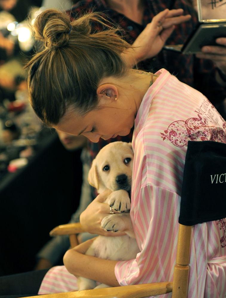 Modelo Behati Prinsloo segura um filhote de cachorro nos bastidores do desfile anual de lingerie da Victoria's Secret, em Nova York, 19 de novembro de 2009