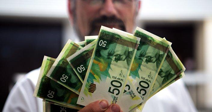 Um funcionário do Banco de Israel com as novas notas de 50 Shekels durante uma coletiva de imprensa na sede do banco em Jerusalém (arquivo)
