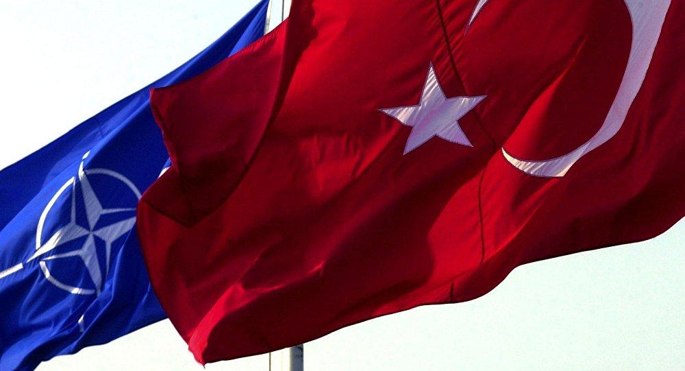 Uma bandeira turca tremula em frente à bandeira da OTAN