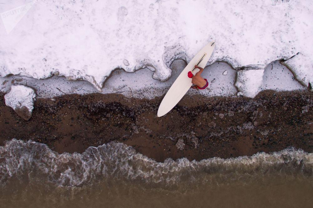 Atleta russo Aleksandr Orlov fecha a temporada de windsurf, efetuando a última manobra nesse ano na represa perto da central hidroelétrica de Novossibirsk, Rússia, com a temperatura do ar em torno de - 5С