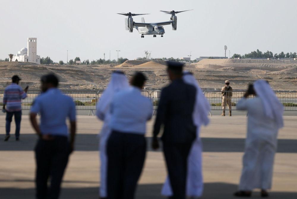 Espectadores assistem ao voo de acrobacia realizado pelo USMC MV-22 durante a apresentação aérea na base de Sakhir ao sul de Manama, Bahrein