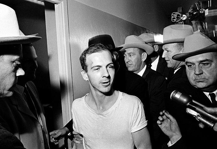 Norte-americano Lee Harvey Oswald fala à imprensa enquanto é conduzido à delegacia de Dallas (EUA) para outra rodada de interrogatórios relacionados ao assassinato do presidente dos EUA, John F. Kennedy, em 23 de novembro de 1963