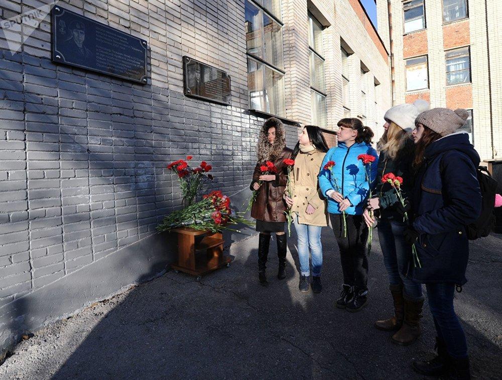 Pessoas com flores junto a placa memorial em honra do fuzileiro naval Aleksandr Pozynich, morto na Síria em novembro de 2015