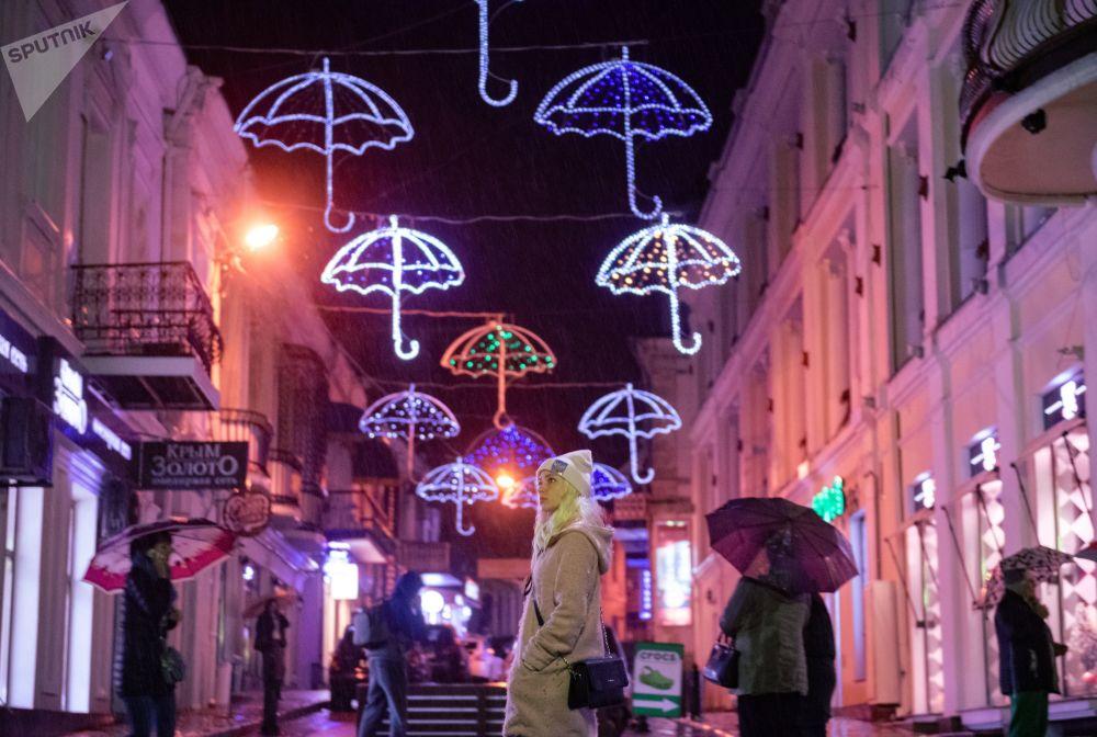 Pedestres em uma rua na cidade russa de Yalta, na Crimeia, durante uma chuva forte