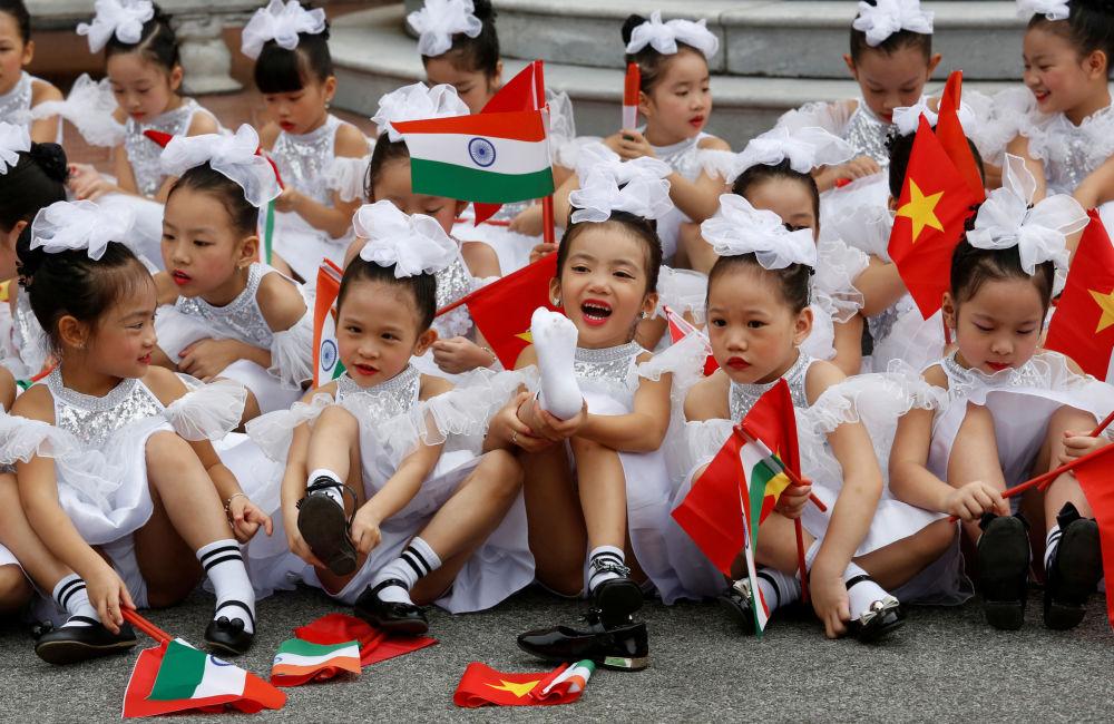 Crianças vietnamitas saúdam o presidente indiano, Ram Nath Kovind, que chegou a Hanói no âmbito de uma visita oficial