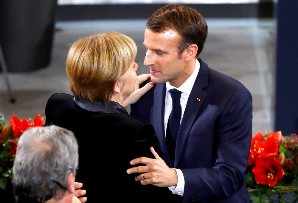 Chanceler alemã, Angela Merkel, abraça o presidente francês, Emmanuel Macron, após discursar no parlamento alemão no Dia do Luto Nacional