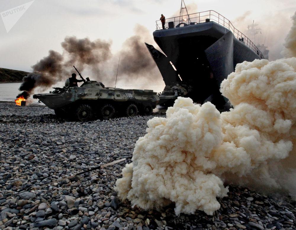 Veículos de transporte blindados com fuzileiros navais em operação anfíbia de treinamento