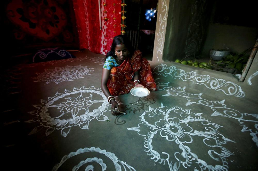 Purnima Shaw, de 27 anos, cria um desenho ritual de pasta de arroz no chão de barro por ocasião do festival Laxmi Puja.