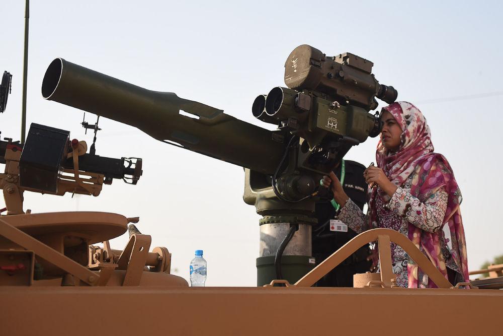 Paquistanesa olha através de  sistema antitanque de defesa aérea na 10ª edição da Exposição e Congresso Internacional da Indústria de Defesa (IDEAS), na cidade de Karachi, Paquistão