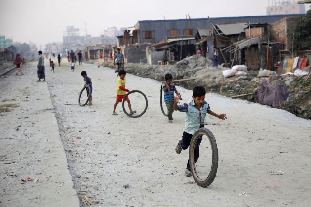 Crianças brincam com pneus na rua em Dhaka, Bangladesh