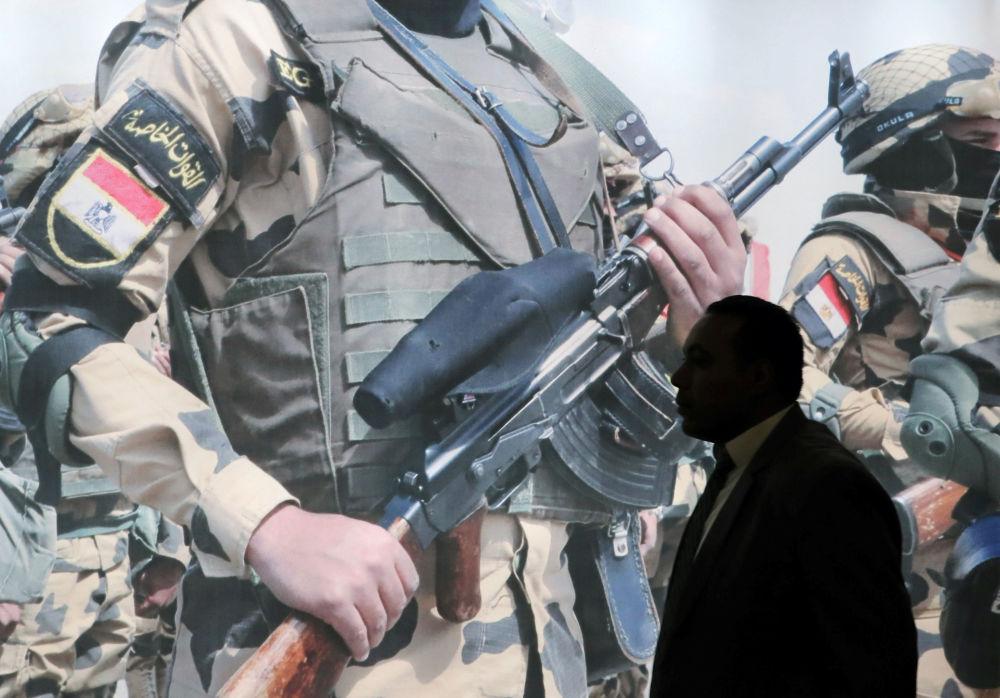 Visitante em frente a um pôster na Feira Internacional de Defesa EDEX 2018 no Egito