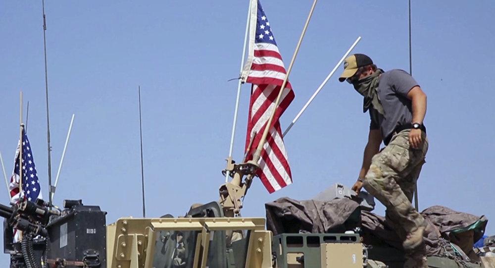 Soldado americano em pé em um veículo blindado.