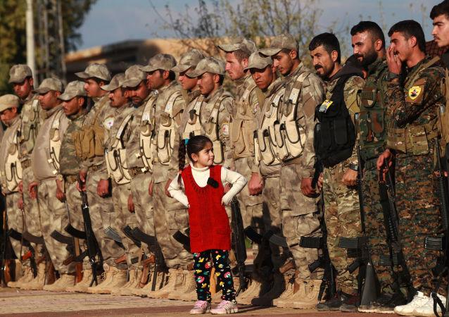 Combatentes das Forças Democráticas da Síria atendendo cerimônia fúnebre de um de seus membros morto durante combates contra o grupo terrorista Daesh