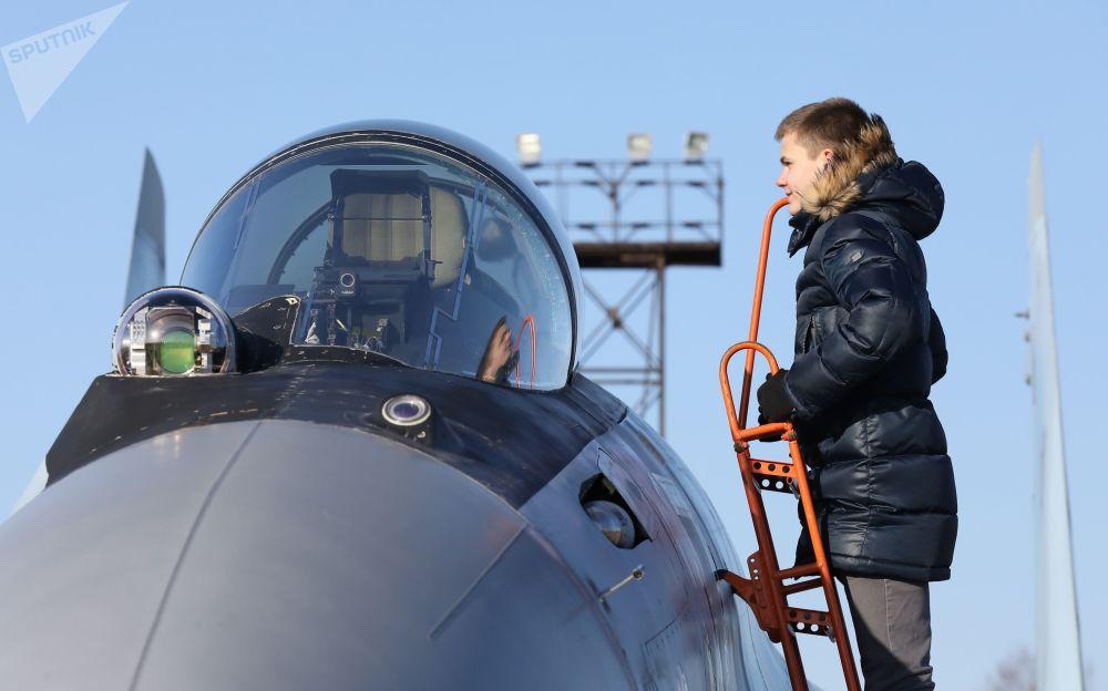 Um jovem examina a cabine de um caça russo Su-35S