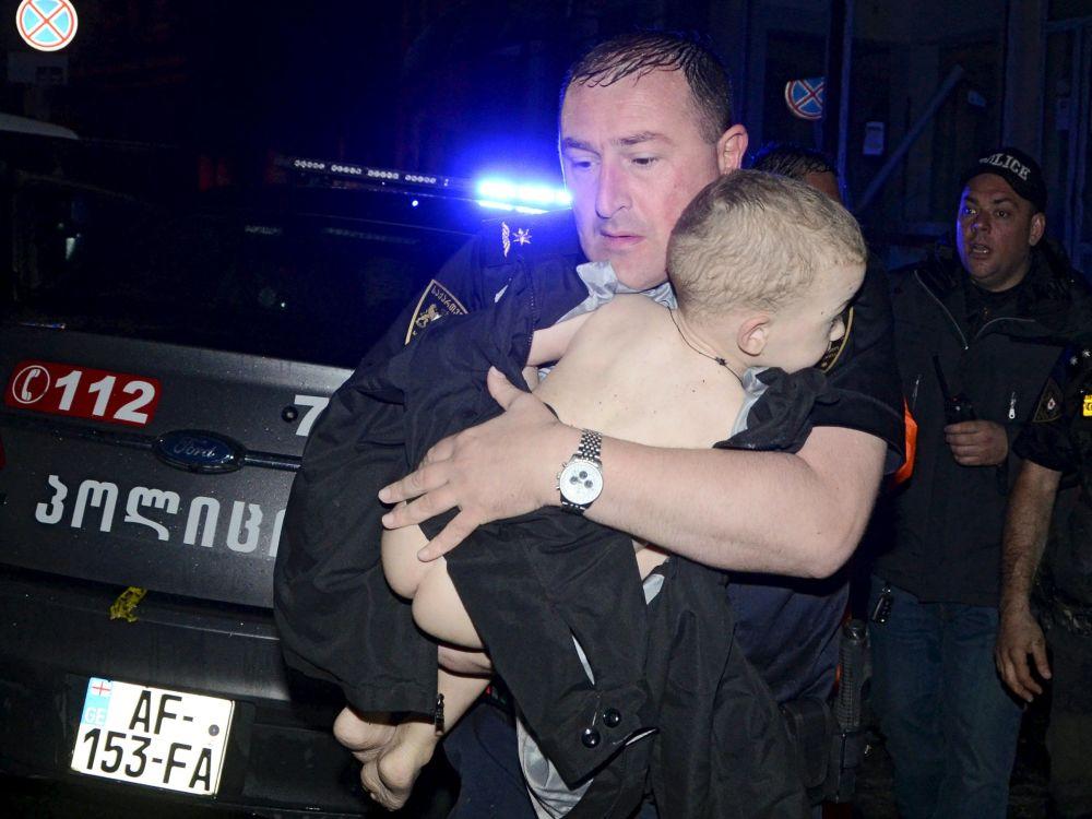 Um socorrista resgata uma criança de uma casa alagada na capital georgiana