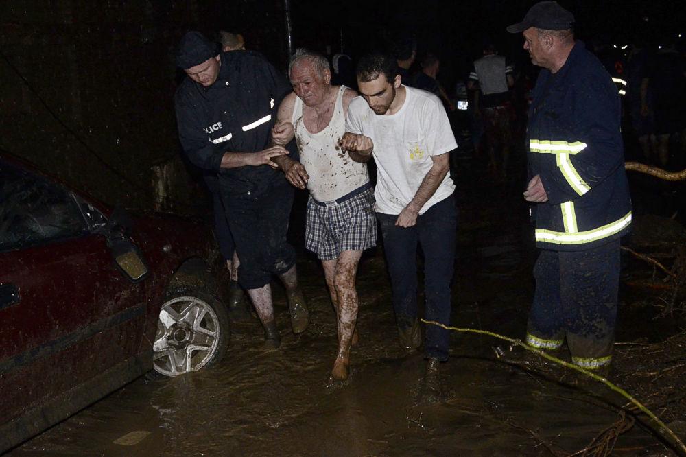 Socorristas ajudam a evacuar uma pessoa idosa de uma área alagada em Tbilisi