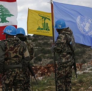 In this Thursday, Dec. 13, Forças de paz da ONU mantêm suas bandeiras em pé ao lado das bandeiras do Hezbollah e do Líbano nos locais onde escavadores israelenses estão trabalhando.2018 photo, UN peacekeepers hold their flag while standing next to Hezbollah and Lebanese flags, at the site where Israeli excavators are working, near the southern border village of Mays al-Jabal, Lebanon