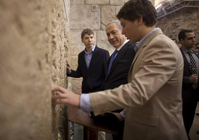 In this Jan. 22, 2013 file photo, Israeli Prime Minister Benjamin Netanyahu, center, prays with his sons Yair, background, and Avner, right, at the Western Wall, the holiest site where Jews can pray, in Jerusalem's Old City.
