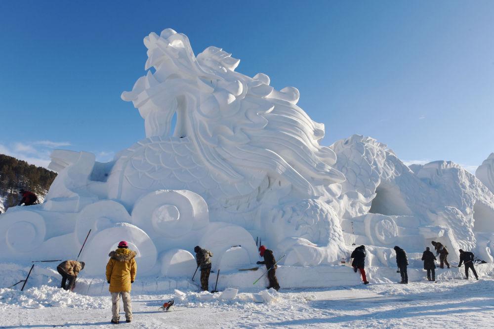 Escultura de um dragão feito de gelo e neve para preparação da temporada turística de inverno na China