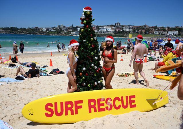 Turistas posam para foto usando gorro de Papai Noel ao lado de uma árvore de Natal na praia de Bondi em Sydney, em 25 de dezembro de 2018