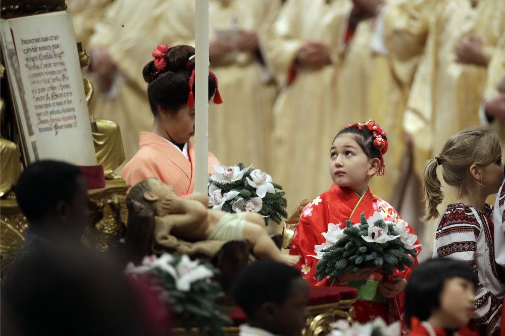 Crianças passam por estátua do menino Jesus no final da missa de véspera de Natal celebrada pelo Papa Francisco na Basílica de São Pedro, no Vaticano, 24 de dezembro de 2018