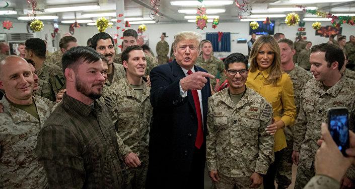 O presidente dos EUA, Donald Trump e a primeira-dama dos EUA, Melania Trump, posam para uma foto durante visita a membros do Exército dos EUA em um refeitório na base aérea de Al Asad.