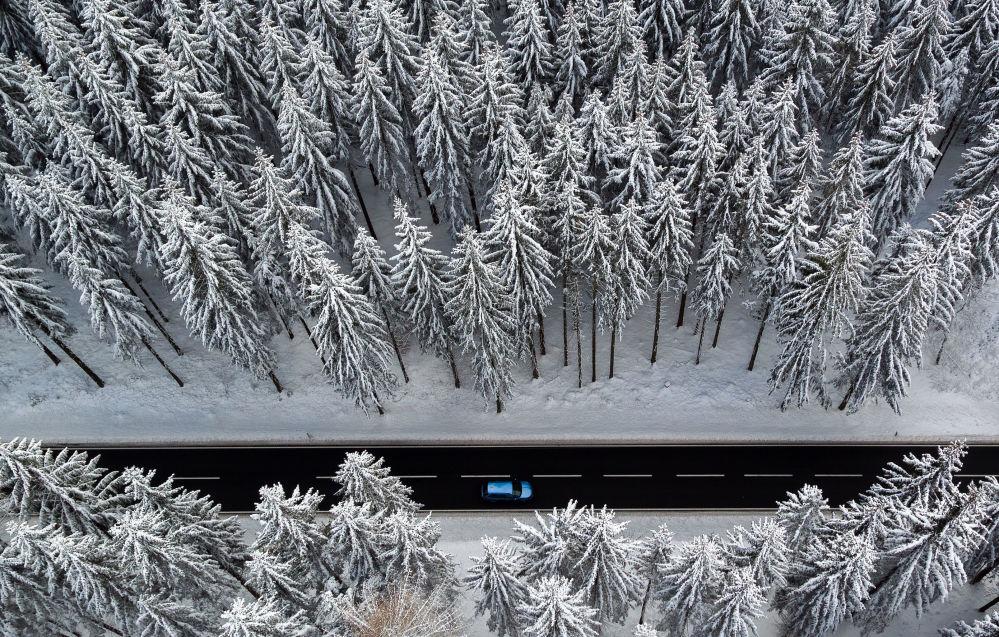 Vista aérea de uma floresta durante o inverno mostra um carro que conduz através da região dos Montes Metalíferos, na Alemanha Oriental, 14 de dezembro de 2018