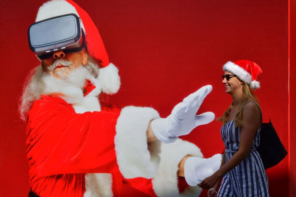 Garota passa por um pôster gigante do Papai Noel em Dubai