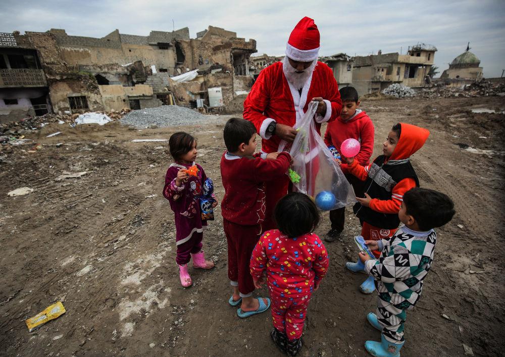Homem vestido de Papai Noel distribui presentes para as crianças, no Iraque