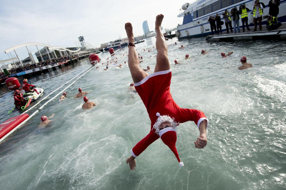 Participante vestindo roupa de Papai Noel pula na água durante a Copa de Natal, em Barcelona