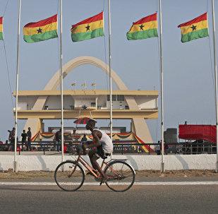 Homem andando de bicicleta ao lado de bandeiras de honra ao presidente de Gana, John Evans Atta Mills, na Praça da Independência em Acra, Gana, 9 agosto de 2012 (foto do arquivo)