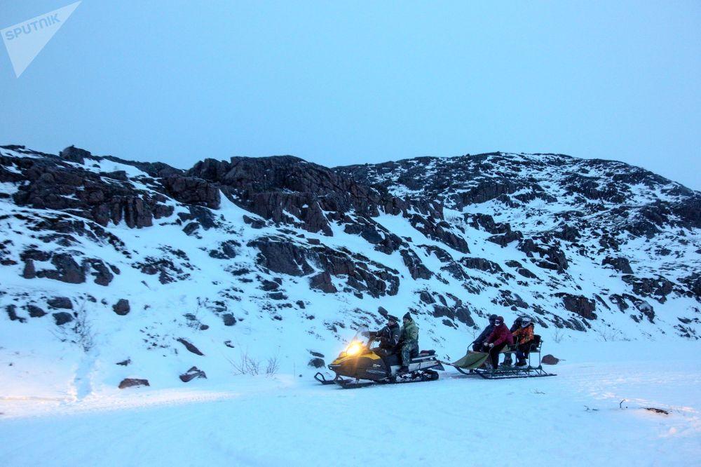 Turistas explorando arredores da península de Kola (Rússia) em motos de neve