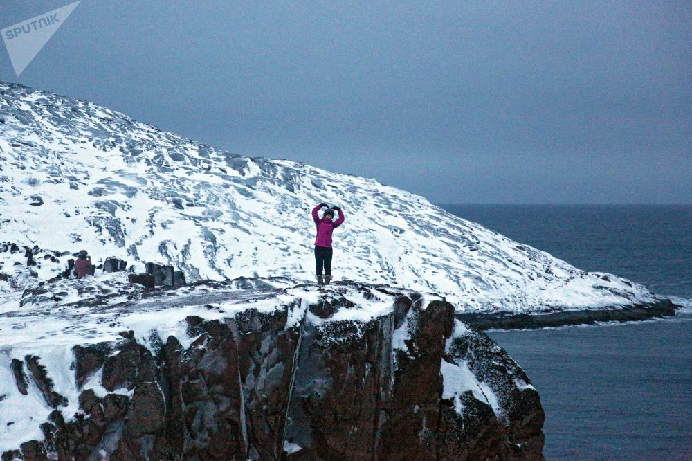 Turista fotografada com vista para o mar, na península de Kola (Rússia)