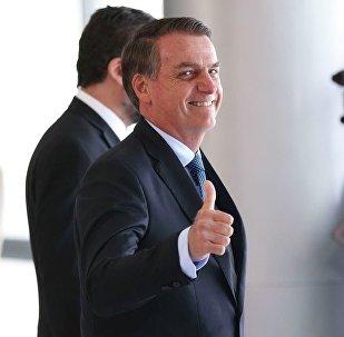 O presidente Jair Bolsonaro acena para os fotógrafos no Palácio do Planalto