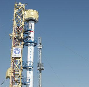 Bandeira iraniana hasteada em frente de foguete portador de satélites iraniano (imagem referencial)