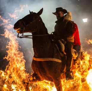 Casal a cavalo passando pelo fogo durante o festival anual Las Luminarias na cidade espanhola de San Bartolomé de Pinares