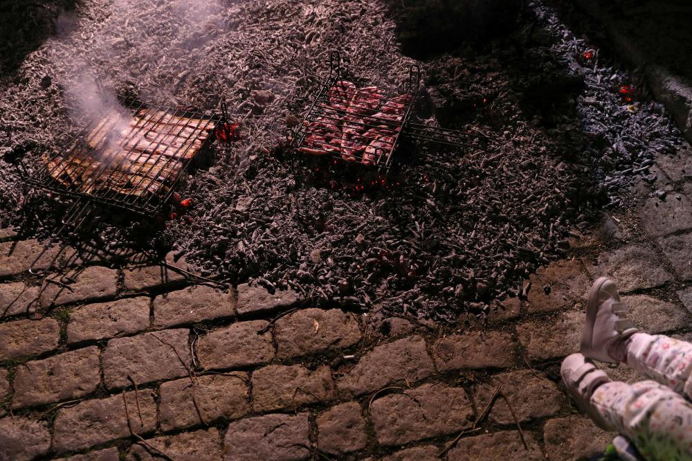 Pessoal assando carne depois do festival anual Las Luminarias na cidade espanhola de San Bartolomé de Pinares