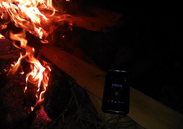 Celular ao lado de fogueira (imagem referencial)