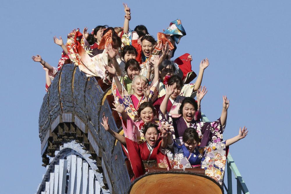 Garotas vestidas de quimono em parque de diversão no Dia da Maioridade, em Tóquio