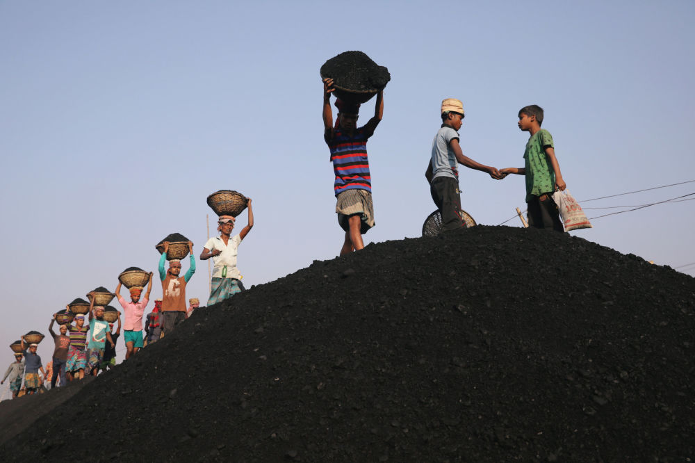 Trabalhadores descarregam balsa com carvão em Daca, Bangladesh, em 13 de janeiro de 2019