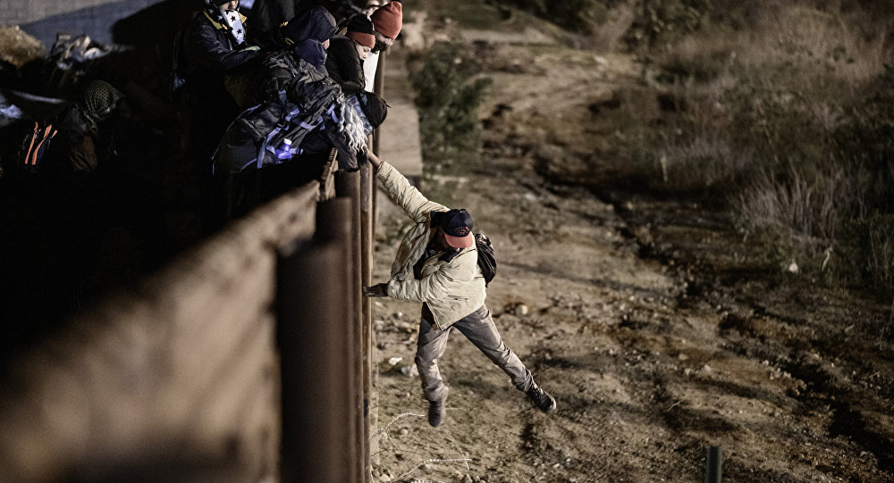 Um migrante em Tijuana, México pula a fronteira para entrar na cidade americana de San Diego, na Califórnia.