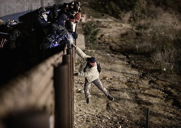 Um migrante em Tijuana, México, pula a fronteira para entrar na cidade americana de San Diego, na Califórnia (arquivo)