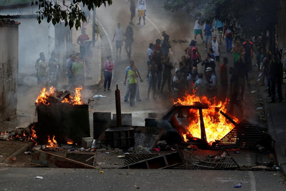 Manifestantes por trás de uma barricada em chamas durante protestos em Caracas, Venezuela