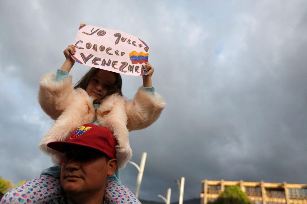 Garota segura cartaz em apoio ao líder da oposição venezuelana, Juan Guaidó, em Bogotá, Colômbia