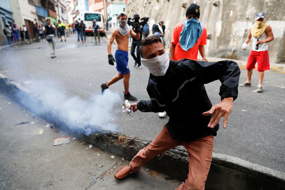 Manifestante joga bomba de gás lacrimogêneo de volta contra Guarda Nacional venezuelana durante protesto em Caracas, Venezuela, em 21 de janeiro de 2019