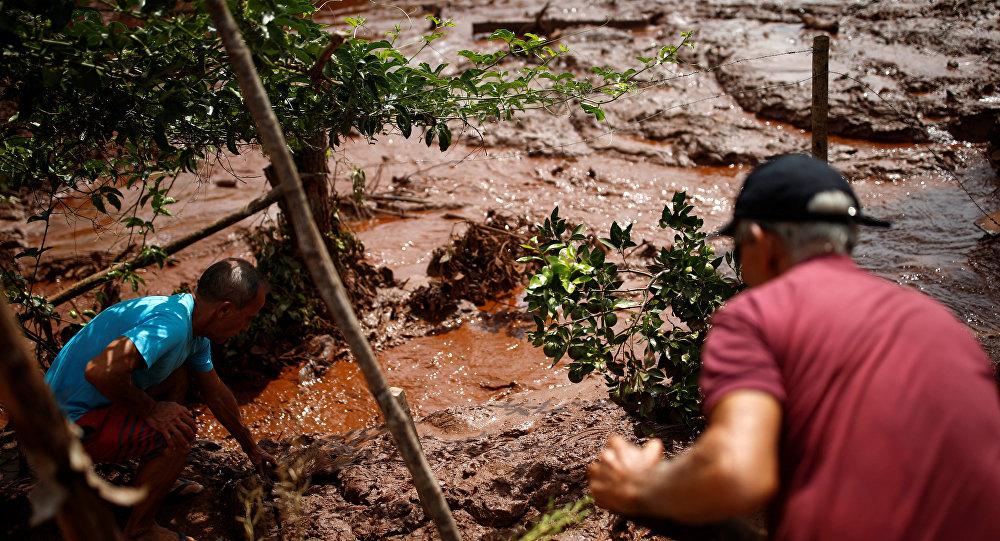 Moradores trabalham em um rio coberto por lama após uma barragem pertencente à mineradora brasileira Vale SA explodir em Brumadinho, Brasil, em 26 de janeiro de 2019.