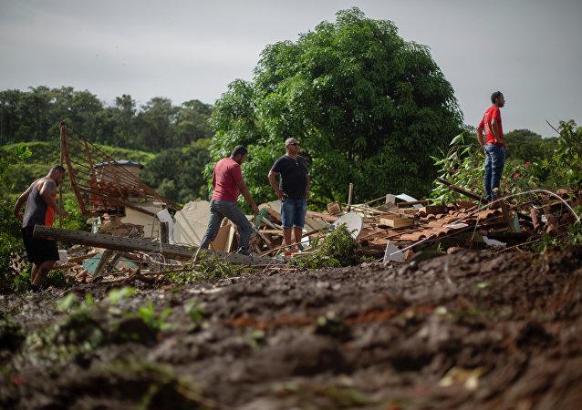 Moradores observam lama depois que uma barragem de propriedade da mineradora brasileira Vale SA explodiu, em Brumadinho