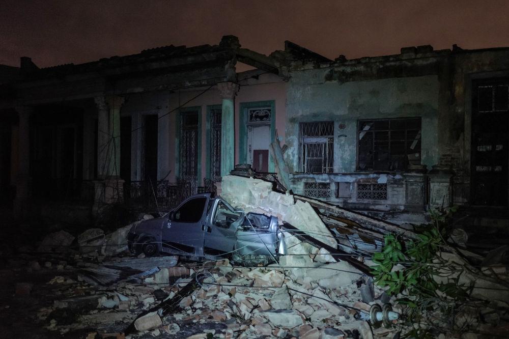 Automóvel esmagado por pedras e outros restos de casas em Havana