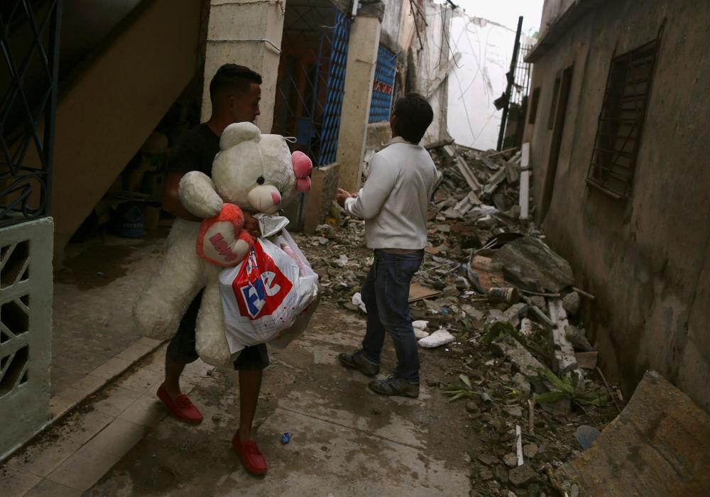 Homem segura bens nas ruas destruídas depois do tornado na capital de Cuba